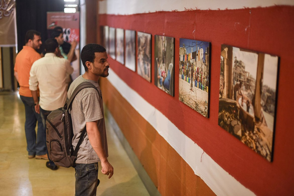 Palestinians in Gaza City attend a photographic exhibition illustrating the suffering of Palestinians living in refugee camps. [Wissam Nassar/Al Jazeera]