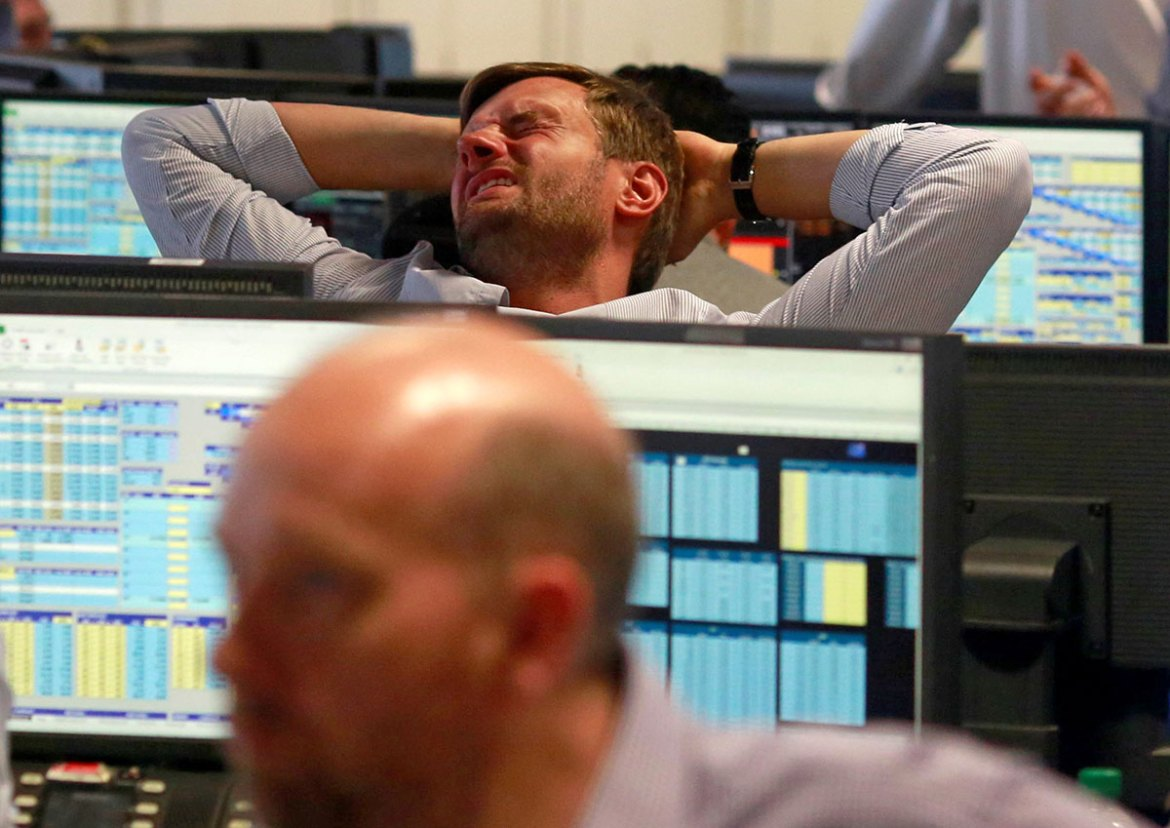 A trader from BGC, a global brokerage company in London's Canary Wharf financial centre, reacts during trading after Britain voted to leave the European Union in the EU Brexit referendum. [Russell Boyce/Reuters]
