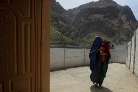 A woman coming from Afghanistan enters the information centre at the border post in Torkham, Pakistan [Reuters]