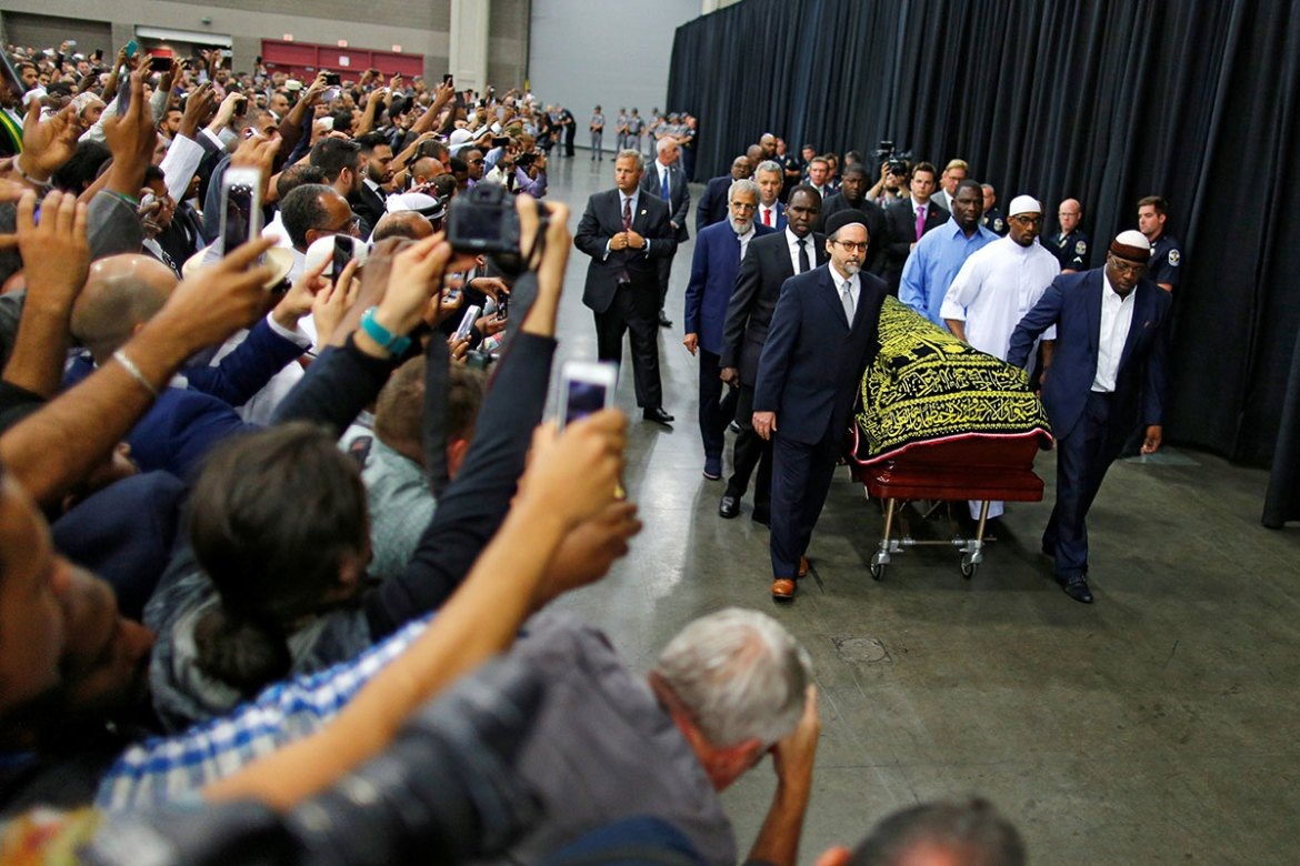 Admirers take photographs as the casket with Ali's body is brought for his jenazah, an Islamic funeral prayer [Carlos Barria/Reuters]