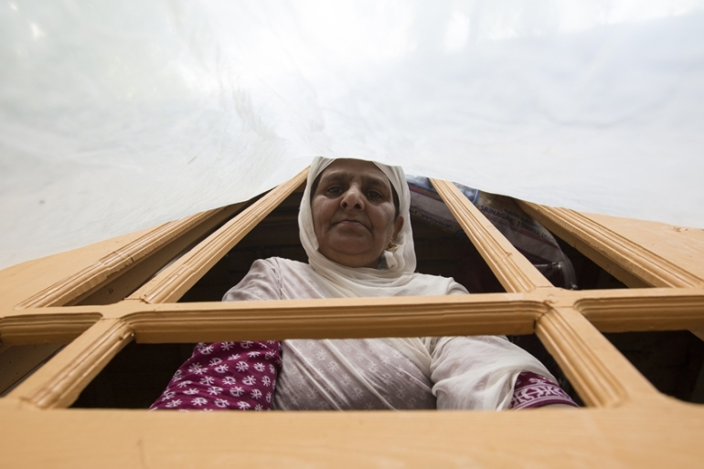 Hafiza looks through a window covered with a polythene sheet. The family doesn't have glass for their windows [Baba Tamim/Al Jazeera]