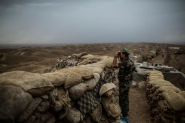 A Peshmerga fighter looks out towards ISIL positions near Kirkuk. [Manu Brabo/MEMO/Al Jazeera]