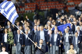 Greece's flag bearer Alexandros Nikolaidis holds the national flag as he leads the contingent in the athletes parade during the opening ceremony of the London 2012 Olympic Games [Mike Blake/Reuters]