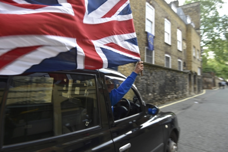 A taxi driver holds a Union flag, celebrating the result of the vote [Toby Melville/Reuters]