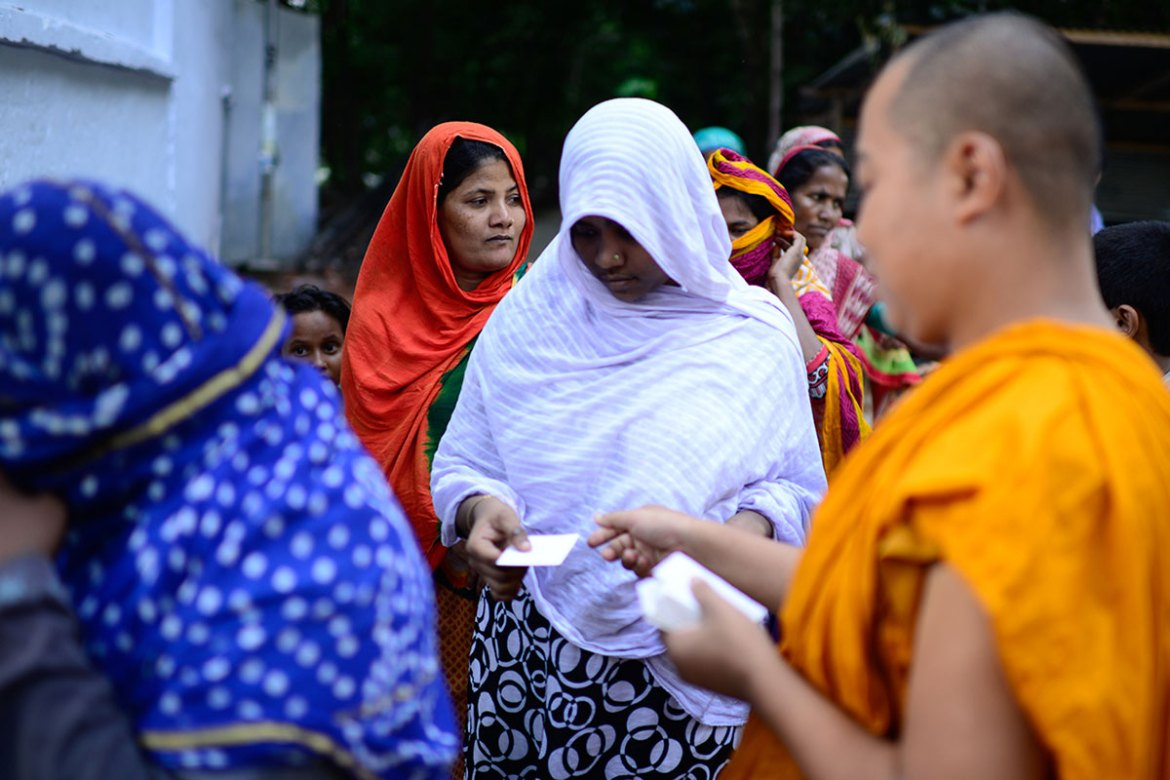Outside the temple, long queues of poor people, mostly women, collect the iftar packets from the monks. [Mahmud Hossain Opu/Al Jazeera]