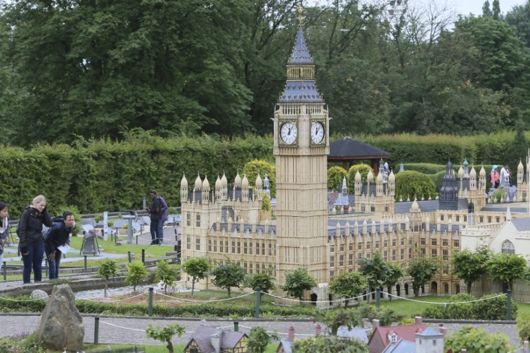 People walk by a miniature model of British Parliament in Mini-Europe miniature park in Brussels, Belgium [EPA]