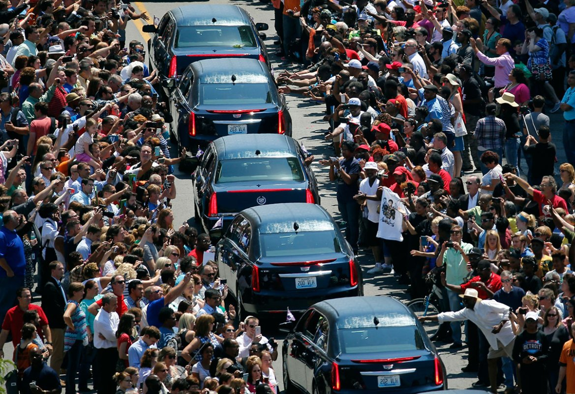 Muhammad Ali's funeral procession passes as onlookers line the street on Friday. [Jeff Roberson/AP]