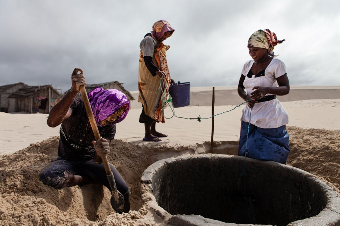 Women dig away sand that had started to cover a well, blown by relentless winds.  Climate change is predicted to increase the intensity of cyclones in this region, making rainfall more erratic and drought more severe in the south of Madagascar. [Garth Cripps/Al Jazeera]
