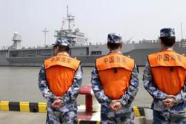 Soldiers from the Chinese People's Liberation Army Navy watch as the USS Blue Ridge arrives at a port in Shanghai [AP]