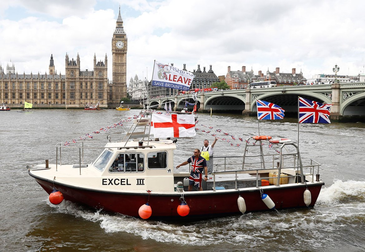 Part of a flotilla of fishing vessels campaigning to leave the European Union sails past Parliament on the river Thames in London. [Stefan Wermuth/Reuters]