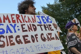 A protester holds a handmade sign at a rally, demanding an end to US support for Israel [Getty]