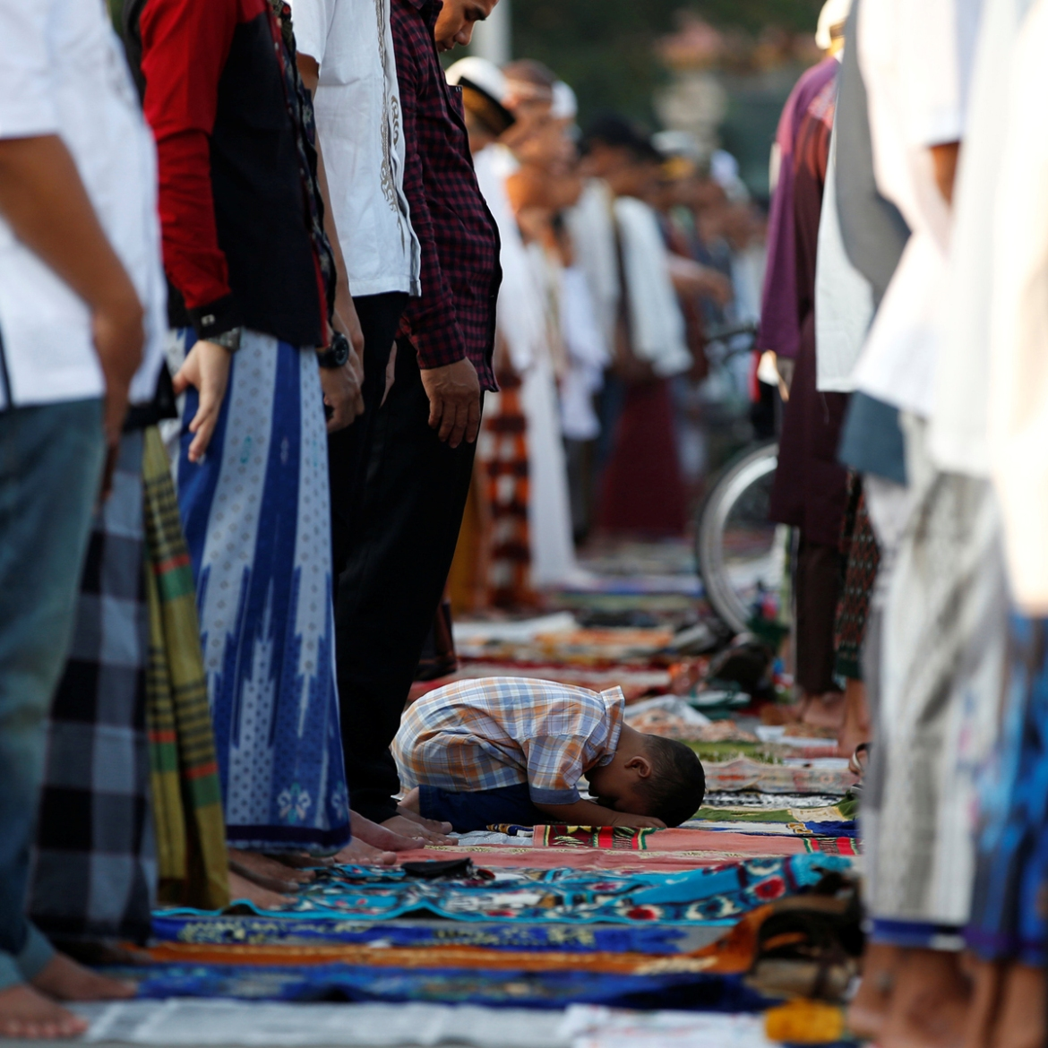 A child attends Eid al-Fitr prayers at Sunda Kelapa port in Jakarta, Indonesia. [Darren Whiteside/Reuters]