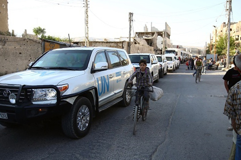 Vehicles of a UN and SARC aid convoy enter the rebel-held town of Douma, east of the Syrian capital Damascus [AFP]