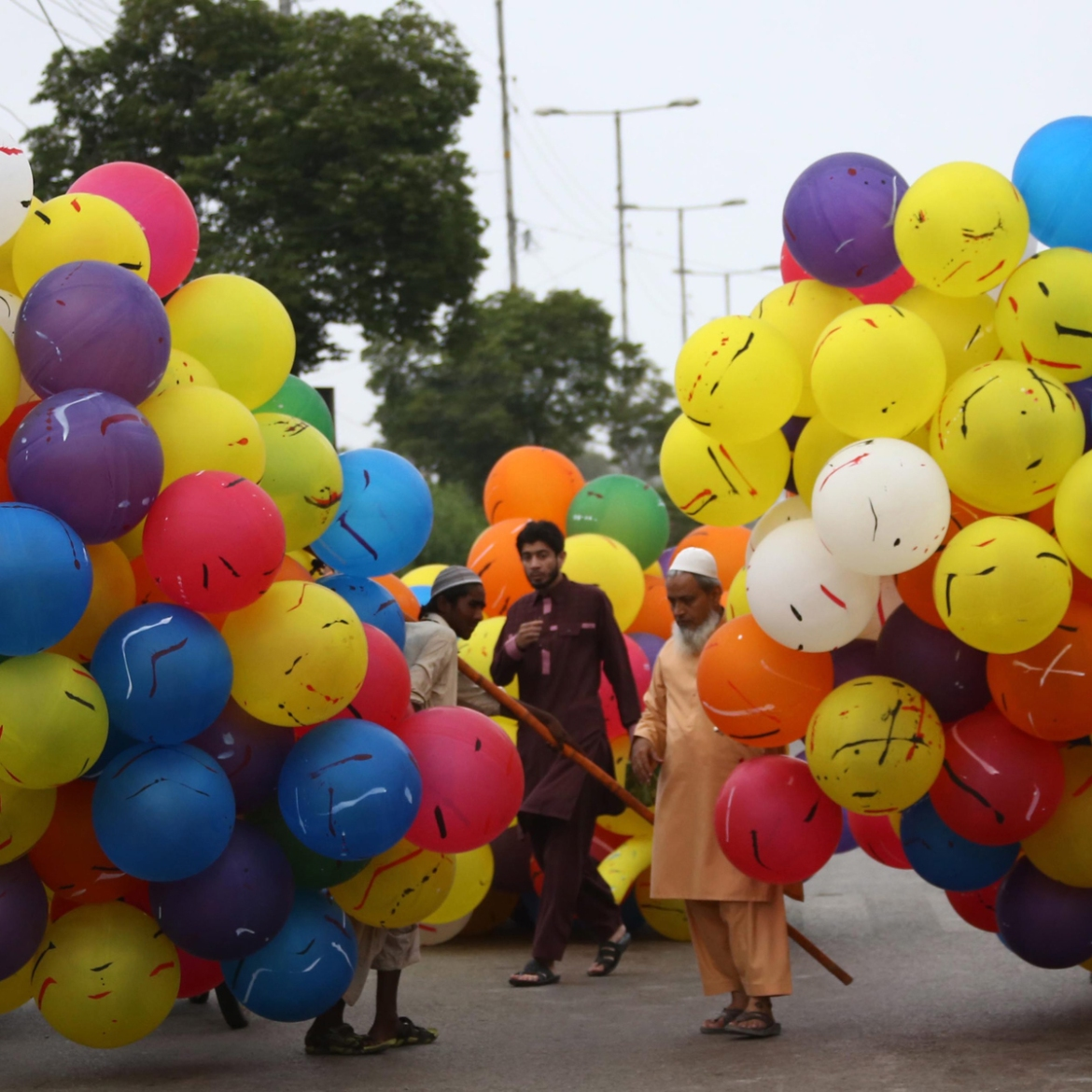 Pakistani men sell balloons after Eid al-Fitr prayers at a mosque in Karachi. [Rehan Khan/EPA]