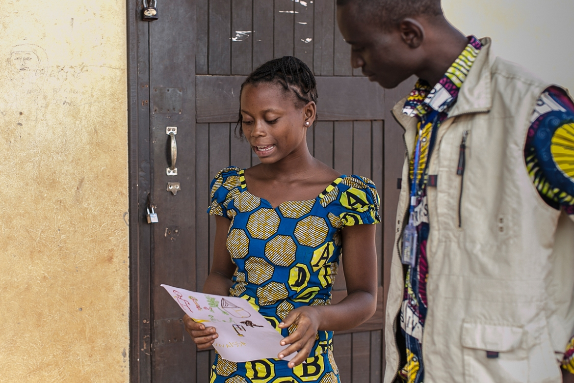 Sylvie, 14, explains her picture to Action Against Hunger's team supervisor Edgar. 'Before the Seleka [arrived] we were in peace and right now we are in anger. That's why I did a picture like this. Everything is broken. There is nothing in our family.' [Samuel Hauenstein Swan/Al Jazeera]