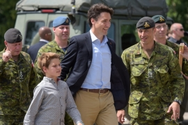 Trudeau and his son walk with Canadian soldiers during a visit to a joint military training of Ukrainian and Canadian soldiers in Ukraine [EPA]