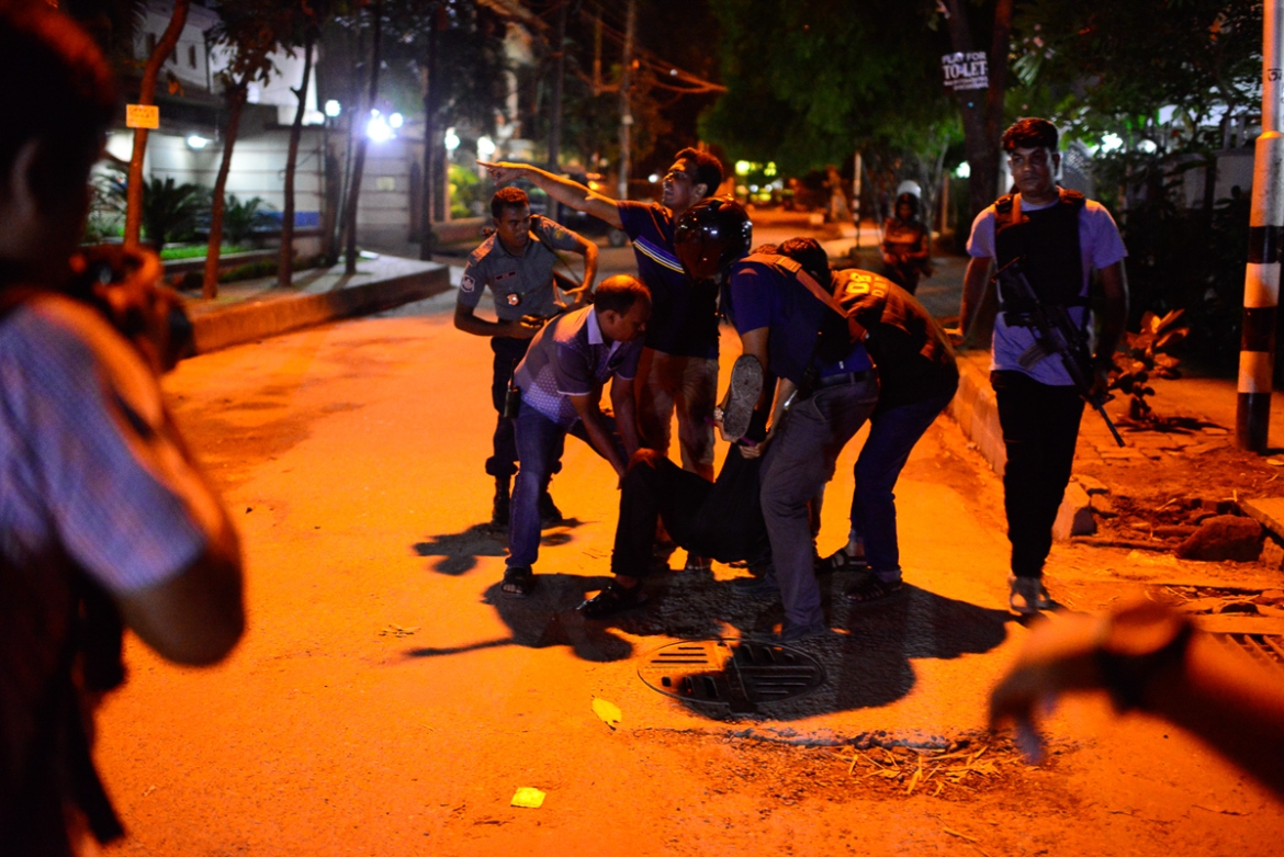 A police officer is wounded by a grenade thrown by the attackers near the Holey Artisan Bakery in Dhaka, Bangladesh [Mahmud Hossain Opu/Al Jazeera]