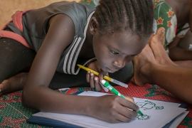 Twelve-year-old Anouk concentrates on her drawing. In their last session, the girls were asked to depict happy times – this time they are sketching out their bad memories and trying to reflect their feelings on paper. [Samuel Hauenstein Swan/Al Jazeera]