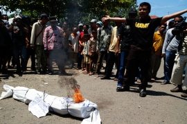 An Indonesian anti-drugs protester burns the effigy of a drug dealer during a rally supporting death row executions [File: EPA]