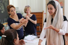 Fatima Ahmadi practises a greeting in Greek during an immersion language course at Melissa, while teacher Vicky Kantzou looks on [John Psaropoulos/Al Jazeera]