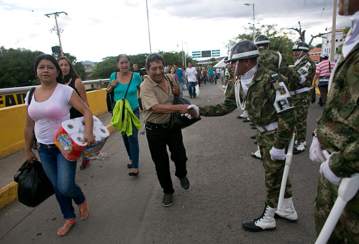 A Venezuelan passes over the Simon Bolivar bridge with others after buying supplies in Cucuta. [Ariana Cubillos/AP]