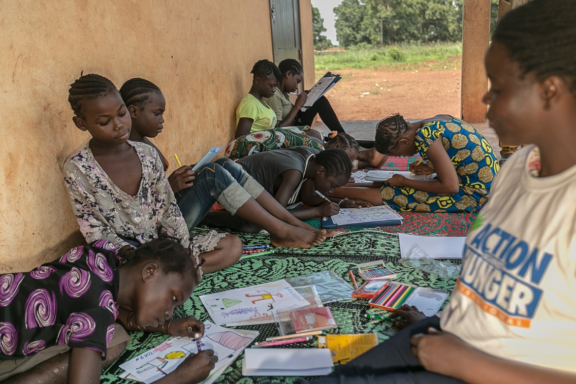 The group draws quietly together, occasionally glancing over at each other's work or reaching for a different coloured pen. Mats have been laid out in the courtyard so that the girls can enjoy some air in the stifling heat. [Samuel Hauenstein Swan/Al Jazeera]