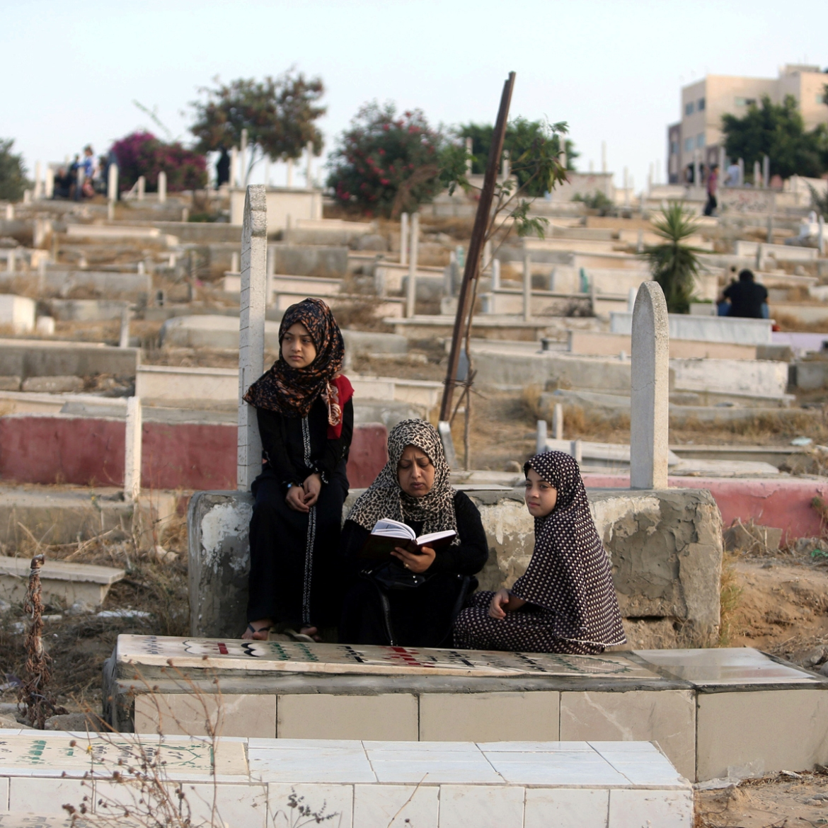 A Palestinian woman reads the Koran next to the grave of her son at a cemetery on the first day of Eid al-Fitr in Gaza City. [Ibraheem Abu Mustafa/Reuters]