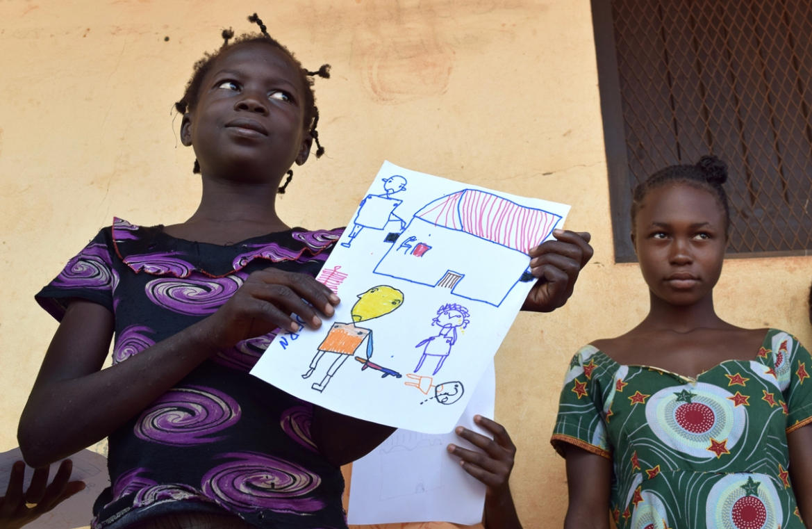 Lucie holds up the picture she has drawn, showing someone being shot dead while another person looks on. At the top of the picture a man is seen kicking in the door of a house. [Paula Dear/Al Jazeera]
