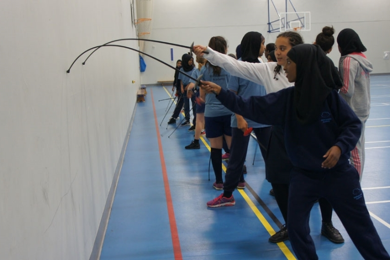 Students from schools across London practise fencing moves on the wall during the taster session at Frederick Bremer School [Zab Mustefa/Al Jazeera]