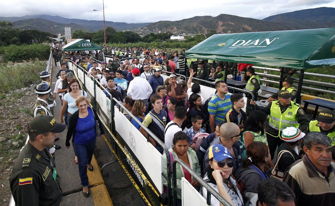 Crowds of people flooded the bridge that links San Antonio to the Colombian city of Cucuta to cross the border on foot. [Gabriel Barrero/EPA]