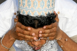 A man performs ablution before the morning prayers for Eid al-Fitr in Colombo, Sri Lanka. [Dinuka Liyanawatte/Reuters]
