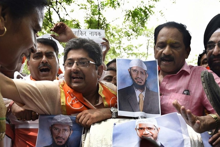 Islamic preacher Zakir Naik, pictured on posters, is the founder of Peace TV [Hindustan Times via Getty Images]