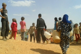 Syrian refugees gather for water at the Rukban refugee camp in Jordan's northeast in June [AP]