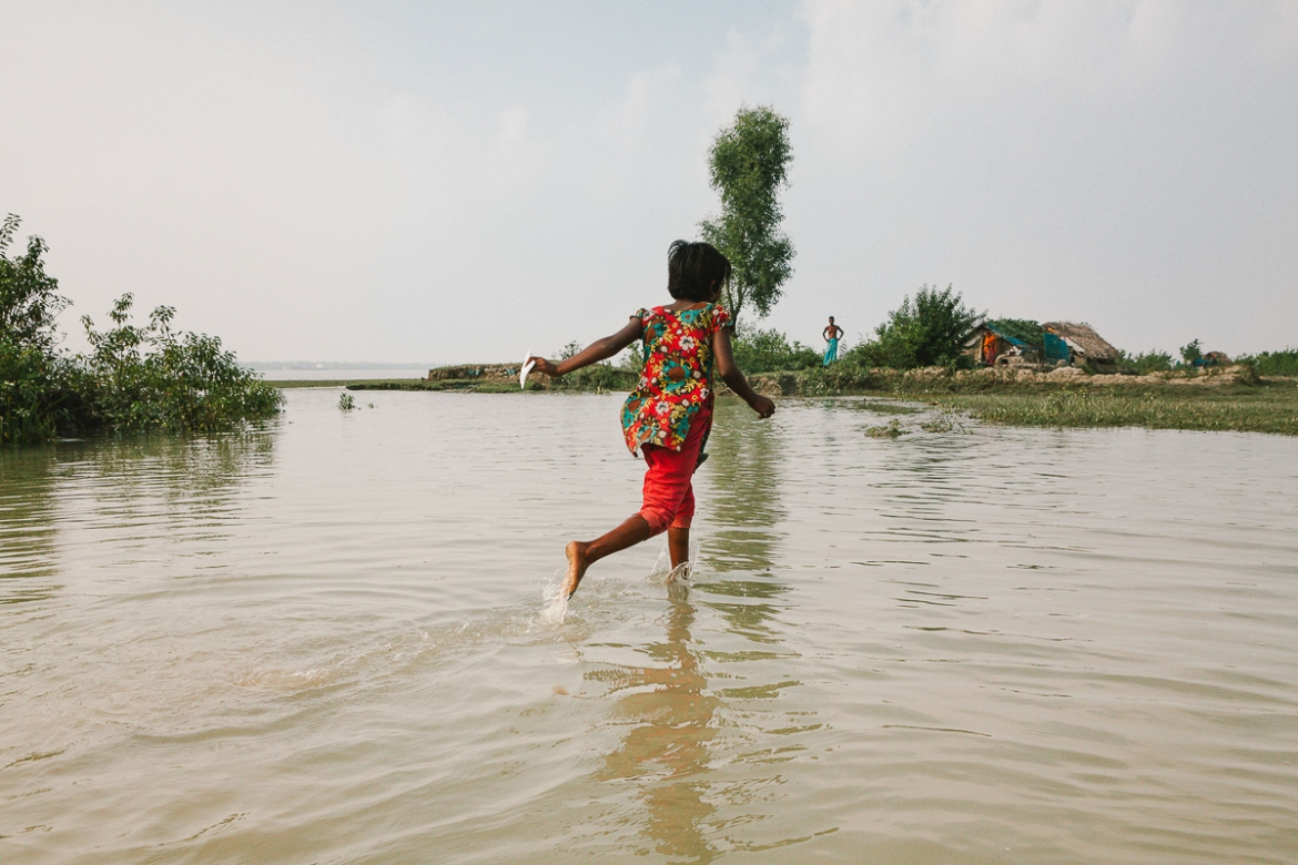 A girl runs across submerged lands in front of her house near the river outside Mongla. One of the biggest impacts for families in southern Bangladesh is the increasing salinity of the water. What was previously fertile farmland is now unfit for growing food, and water that was once fit for drinking has become salty. [Karim Mostafa/Al Jazeera]