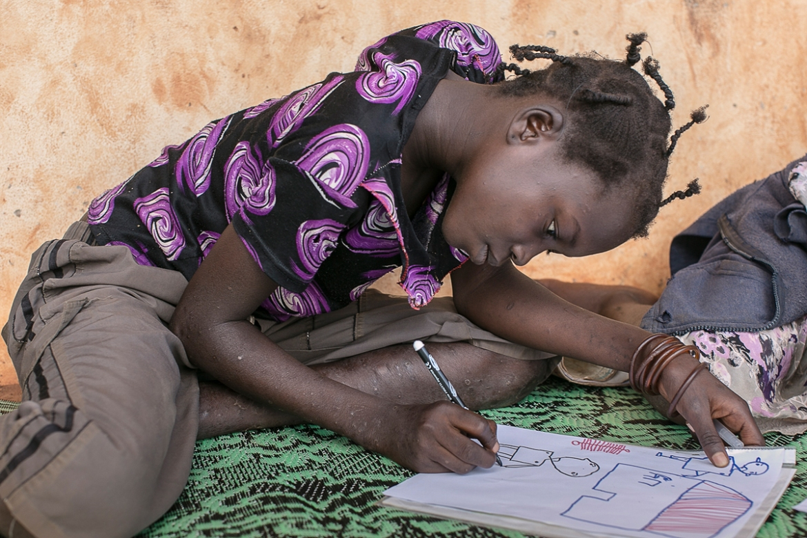 Lucie, 13, adds a gun to the hand of the man she has drawn. Gobongo school teaches pupils from areas of Bangui that are seeing a gradual return of displaced people, who fled violence or had their homes burned down. With 4,000 pupils, class sizes can be as large as 150. [Samuel Hauenstein Swan/Al Jazeera]