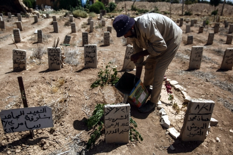 A worker in the cemetery of Douma drops some water and put a green branch on the tomb a volunteer who died while helping people in Zamalka during the chemical attack, Douma, in August 2016 [EPA]