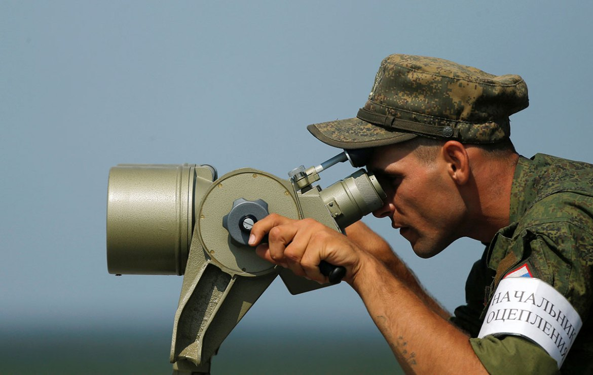 A Russian servicemen uses binoculars during a competition of the International Army Games 2016 at a range in the settlement of Alabino outside of Moscow. [Maxim Shemetov/Reuters]
