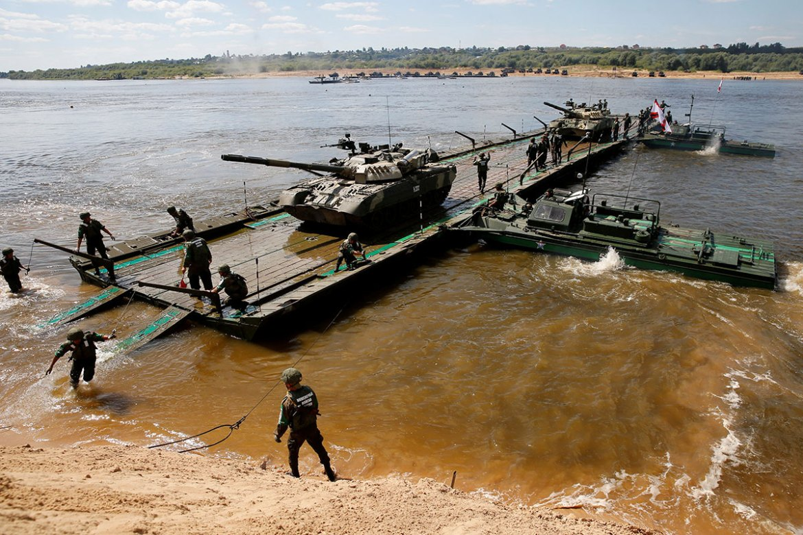 Russian crew members transport T-80 tanks on a pontoon bridge during the Open Water competition for pontoon bridge units in the city of Murom, Russia. [Maxim Zmeyev/Reuters]