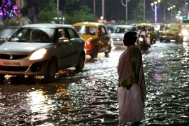 Indian commuters wade through a flooded street during heavy shower in Calcutta, eastern India [EPA]