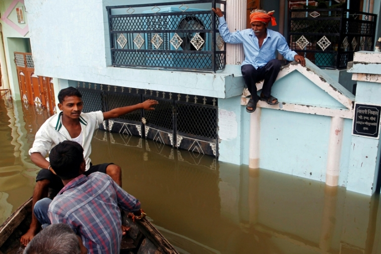 A man sits on the wall of his flooded house as a boat arrives to evacuate him in a residential area of Allahabad [Reuters]