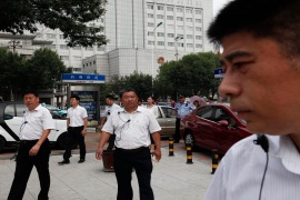 Chinese men in plain clothes, believed to be security staff, follow journalists outside Zhou's trial [AP]