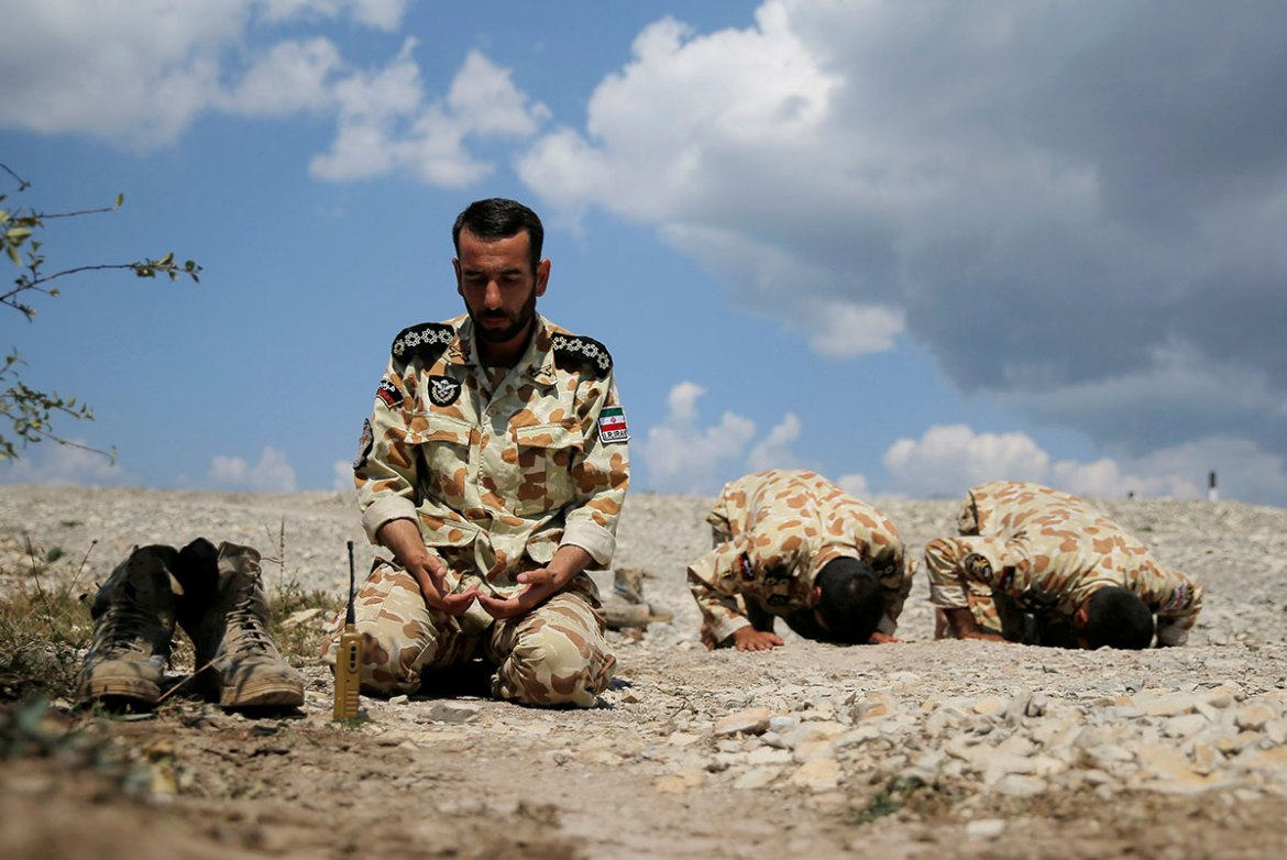 Iranian servicemen pray during the Paratrooper's platoon competition for airborne squads, part of the International Army Games 2016, at the Rayevsky shooting range outside the Black Sea port of Novorossiysk. [Maxim Shemetov/Reuters]