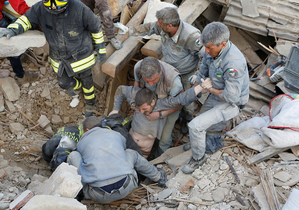 A man is pulled out alive from from beneath rubble after the earthquake hit Amatrice. [Remo Casilli/Reuters]