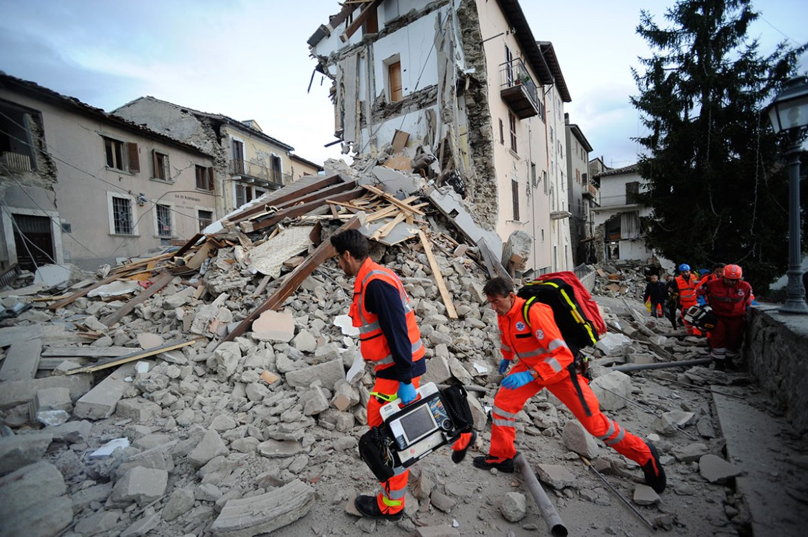Rescuers search a crumbled building in Arquata del Tronto, in the Marche region of central Italy. [Sandro Perozzi/AP]