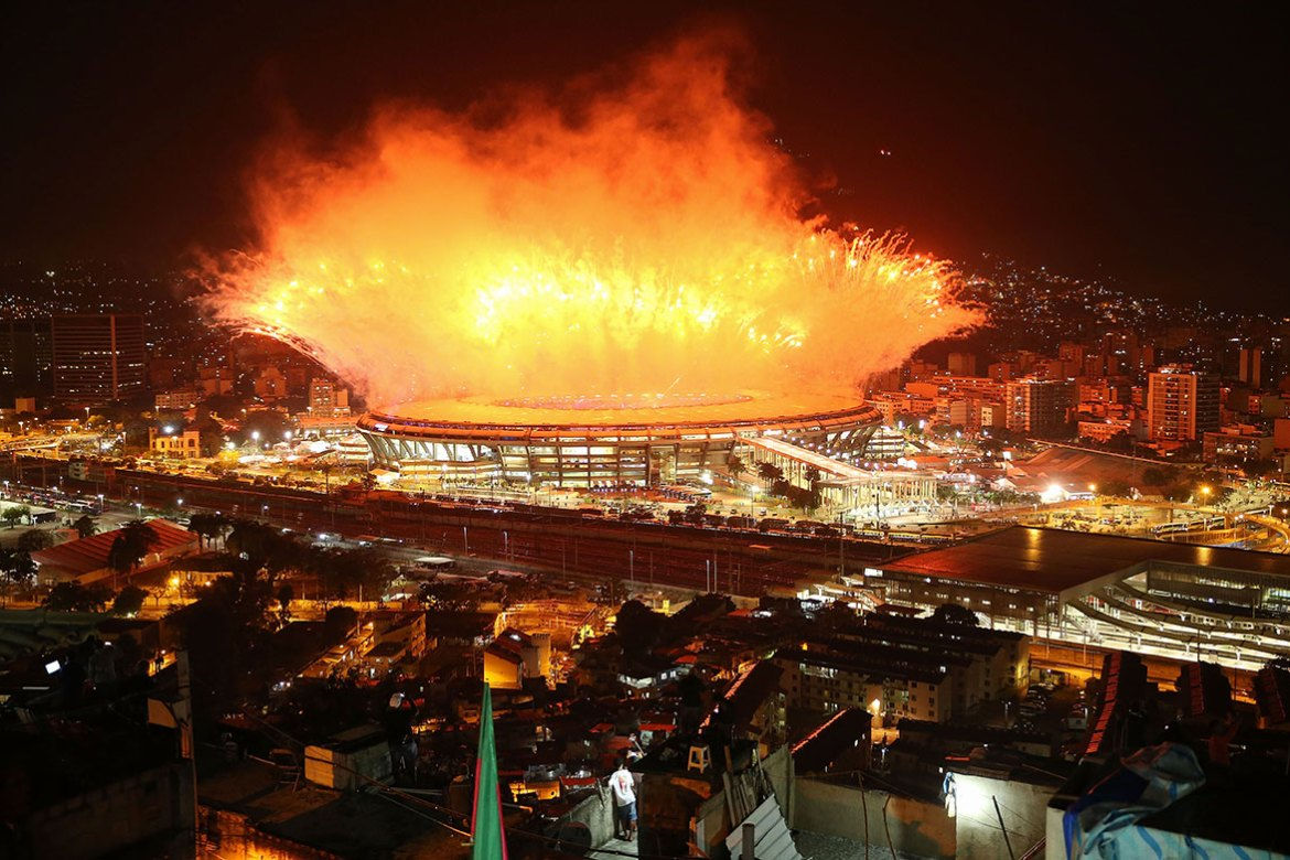 Fireworks formed part of the opening ceremony at Maracana stadium with the Mangueira 'favela' community in the foreground. [Mario Tama/Getty Images]