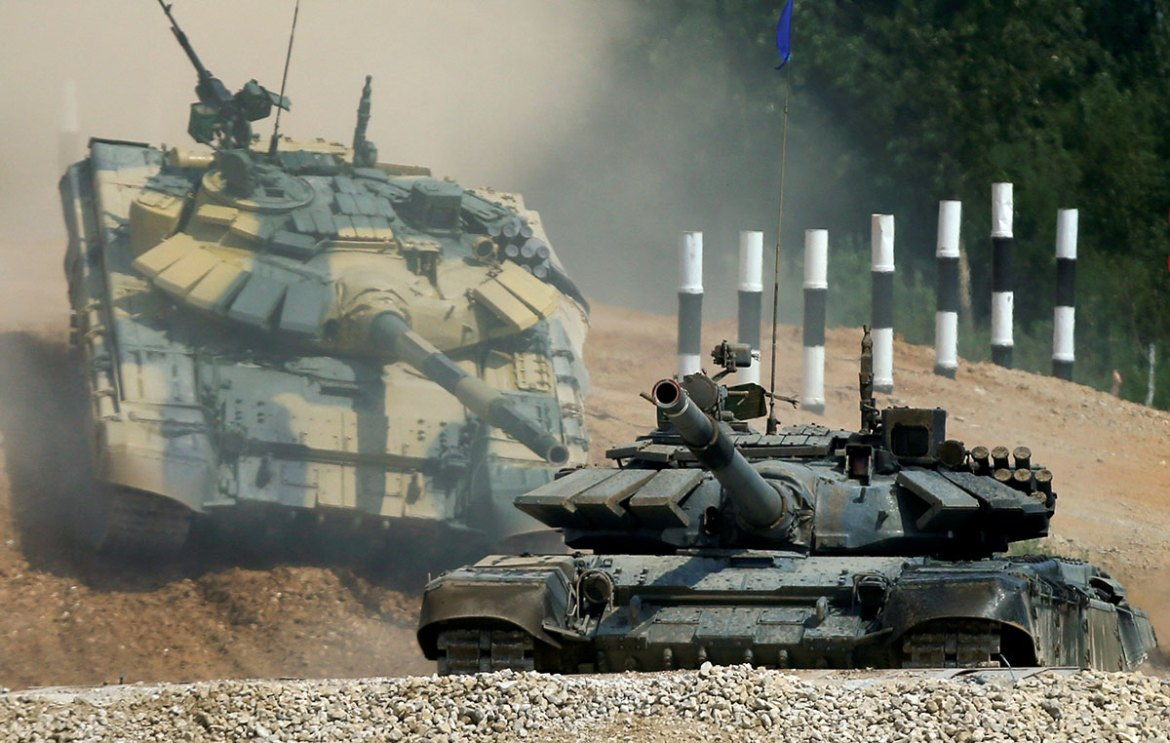 T-72 tanks, operated by crews from Kuwait (front) and Nicaragua, drive during the Tank Biathlon competition, at a range in the village of Alabino outside Moscow. [Maxim Shemetov/Reuters]