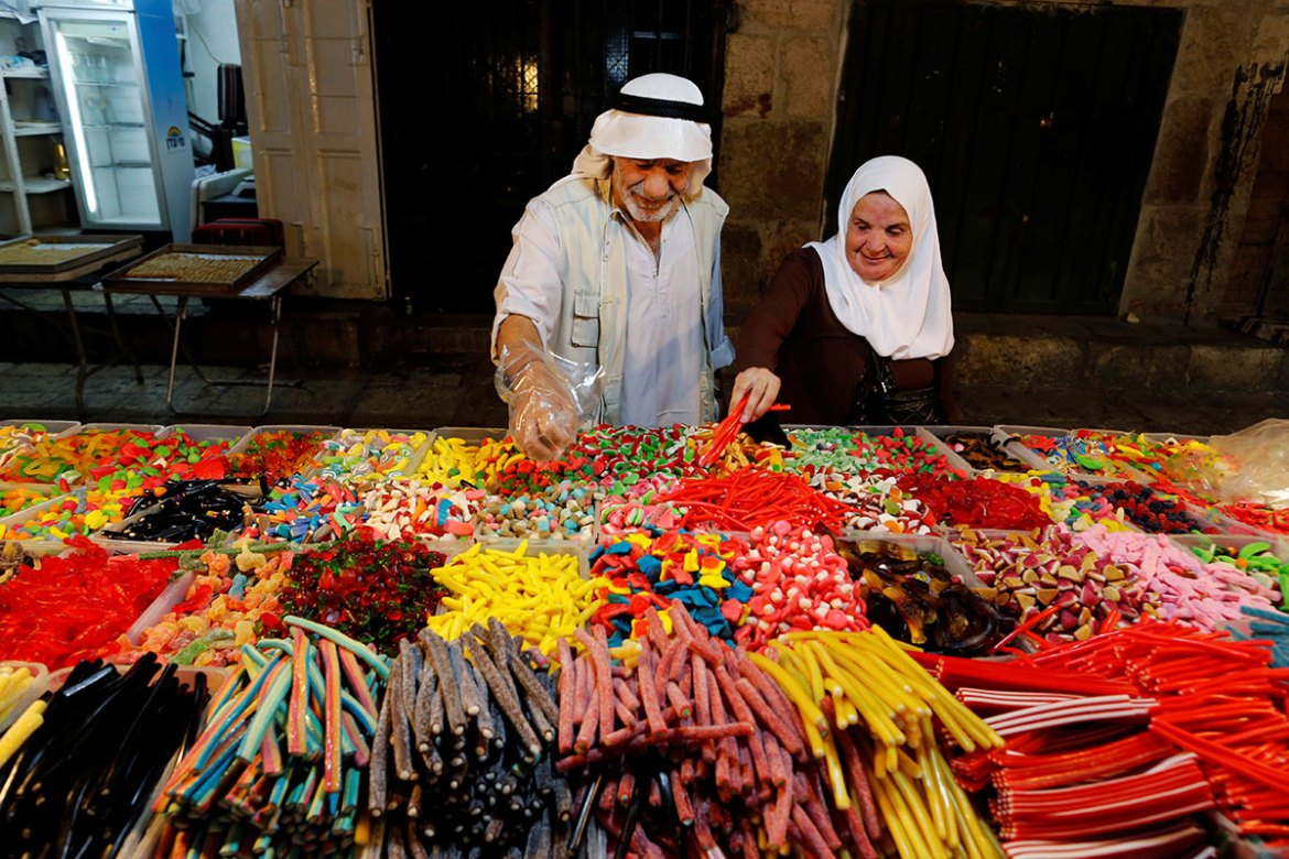 People buy sweets in Jerusalem's Old City before the Muslim holiday. [Ammar Awad/Reuters]