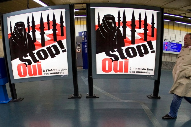 A man passes by a Swiss People's Party poster that's against women wearing the veil [Salvatore di Nolfi/EPA]