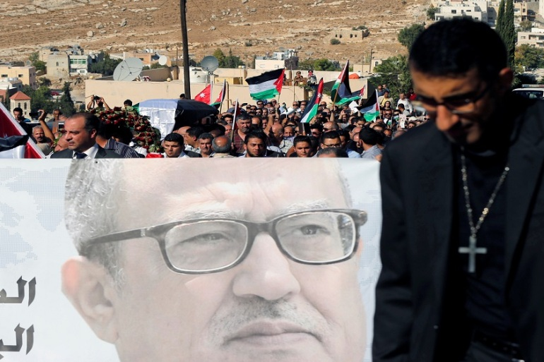 Activists hold a picture of Jordanian writer Nahed Hattar on Wednesday at his funeral [Muhammad Hamed/Reuters]