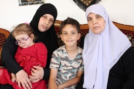 Nirmeen, Iyad's wife, and Shukria, his mother, sit with the couple's two children in the Hamed family home in Silwad [Nigel Wilson/Al Jazeera]